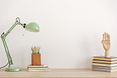 Pastel mint colored lamp on wooden desk with books, copy space on empty white wall