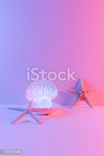 istock Pastel neon blue and pink light paint on seashell and pearl decorate with star fish 1124737252