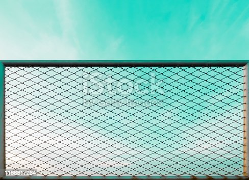 pastel ocean blue color sky and white cloud background texture with steel rusty industrial chain link fence wire pattern enclosure protection foreground with copy space