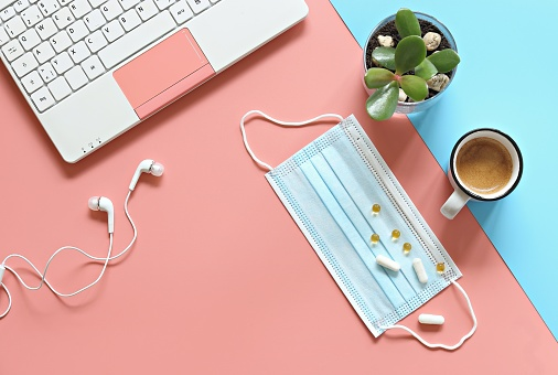 Pastel office desk table with laptop , headphones, protective mask, cup of coffee and small succulent plant on colored background.