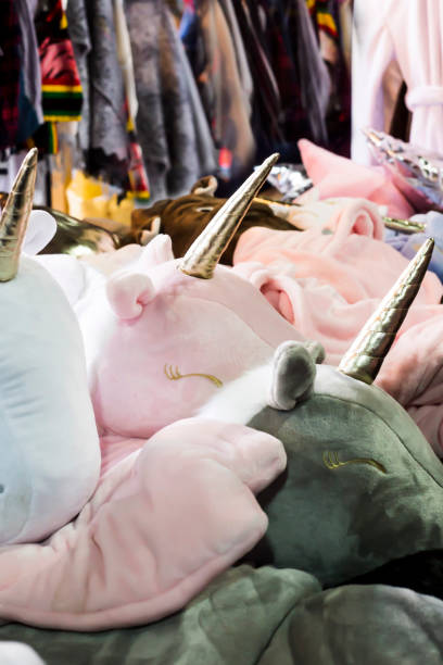 pastel pink and blue heads of unicorns with golden horns. unusual cushions for children and for the interior. trade at the fair - unicorn bed imagens e fotografias de stock