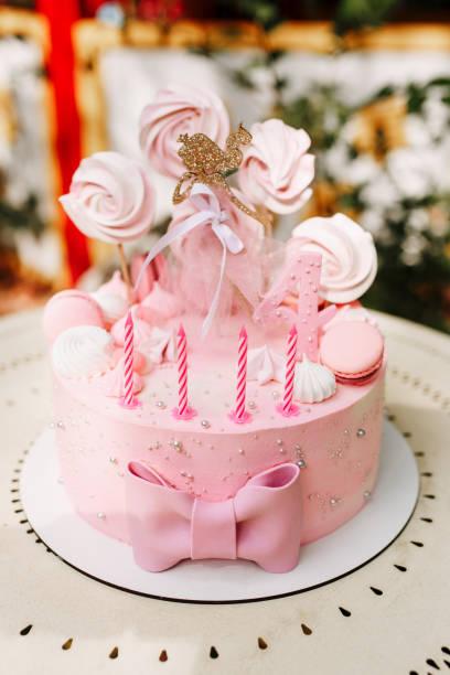 pastell rosa baby geburtstagstorte mit kerzen und streusel dekor. nummer vier jahre - prinzessinnen torte stock-fotos und bilder