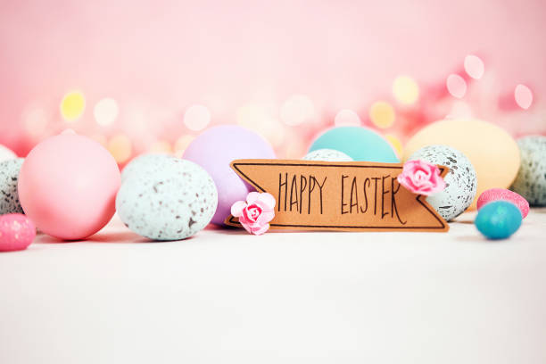 Pastel pink background with message and pastel eggs for Easter stock photo