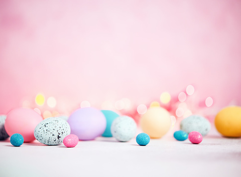 Pastel pink background with pastel eggs for Easter