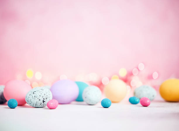 pastel pink background with pastel eggs for easter - easter foto e immagini stock