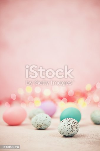 istock Pastel pink bokeh background with pastel eggs for Easter 926943220