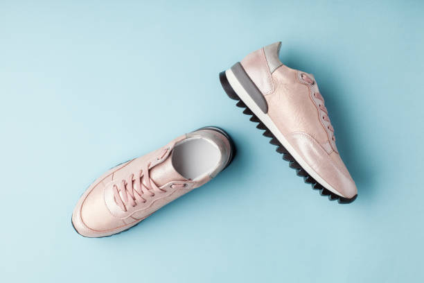 Pastel pink female sneakers on blue background. stock photo
