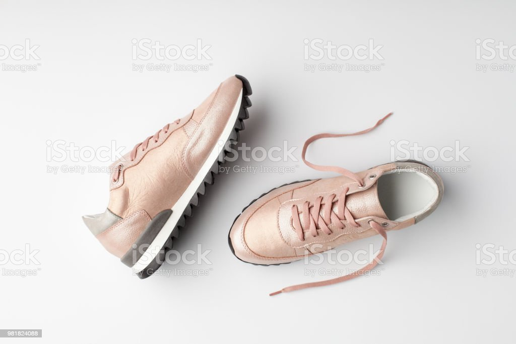 Pastel pink female sneakers on white background. Pastel pink female sneakers on white background. Flat lay, top view minimal background. Adult Stock Photo
