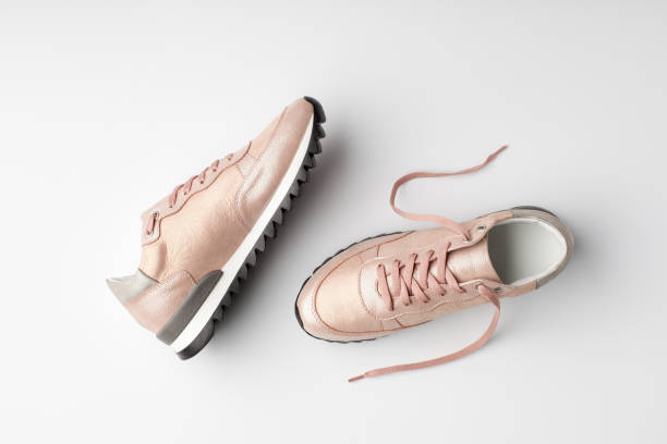 Pastel pink female sneakers on white background. stock photo