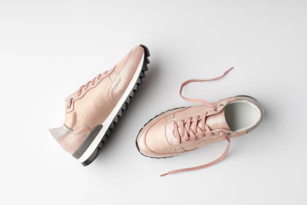 pastell rosa weibliche turnschuhe auf weißem hintergrund. - rosa training stock-fotos und bilder