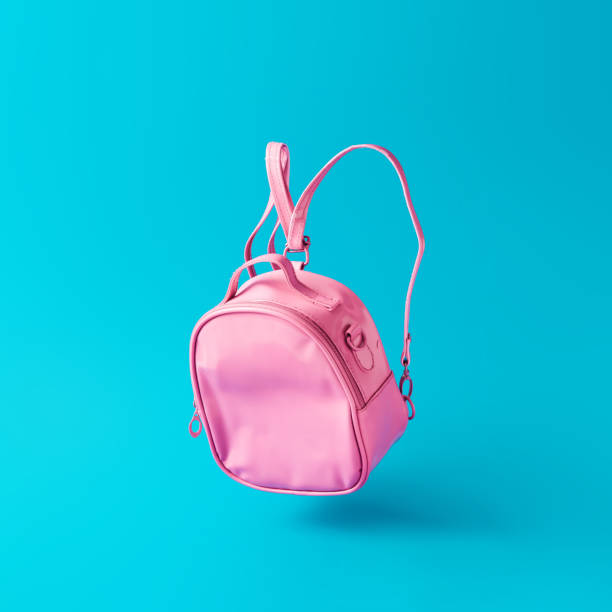 Pastel pink school bag floating on sky blue background. Surreal modern still life. Back to school minimal concept. school supplies border stock pictures, royalty-free photos & images