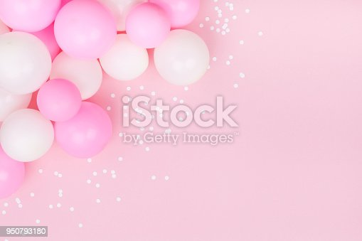 950793576 istock photo Pastel pink table with colorful balloons and confetti for birthday top view. Flat lay. 950793180
