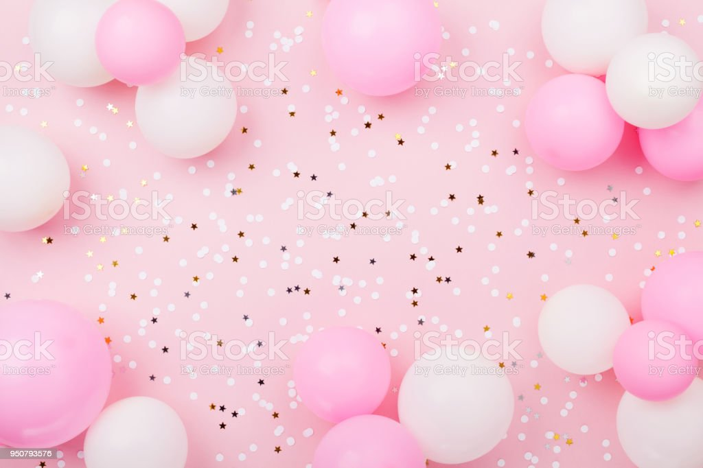 Pastel pink table with frame from balloons and confetti for birthday top view. Flat lay. stock photo