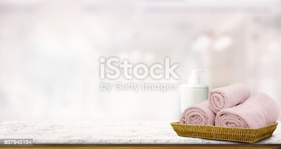 istock Pastel pink towels in basket on top wood table with copy space on blurred bathroom background.