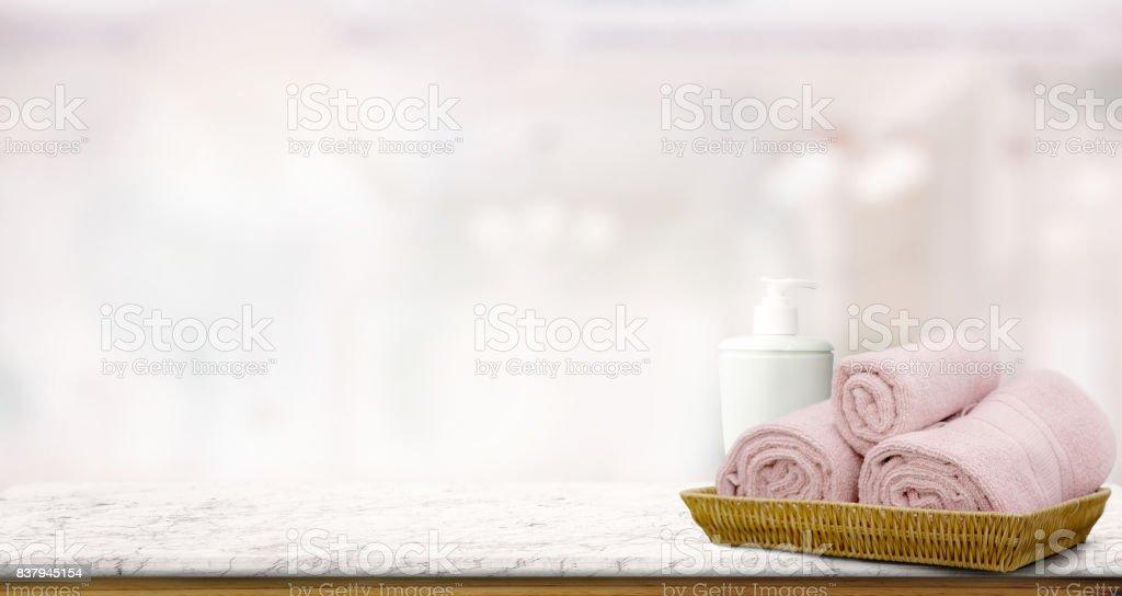 Pastell rosa Handtücher im Korb am oberen Holztisch mit textfreiraum auf unscharfen Bad Hintergrund.