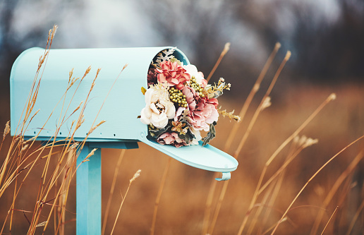 Pastel teal mailbox with bouquet of flowers