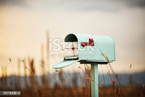 Pastel teal mailbox with stack of love letters, with heart seal
