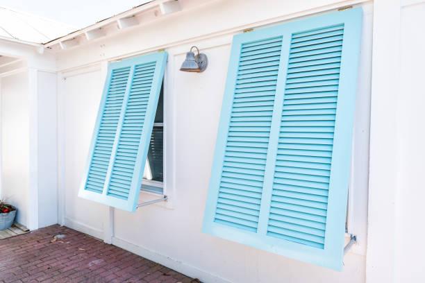 파스텔 터키석 블루 다채로운 허리케인 창 셔터 근접 촬영 아키텍처 화창한 날, 그린 홈 플로리다 해변에 집의 외면 열 - 겉창 뉴스 사진 이미지