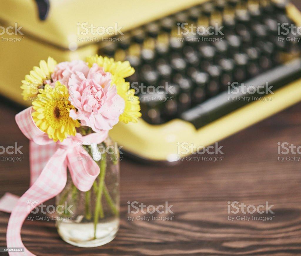 Pastel vintage yellow typewriter with simple bouquet of flowers pastel vintage yellow typewriter with simple bouquet of flowers royalty free stock photo izmirmasajfo