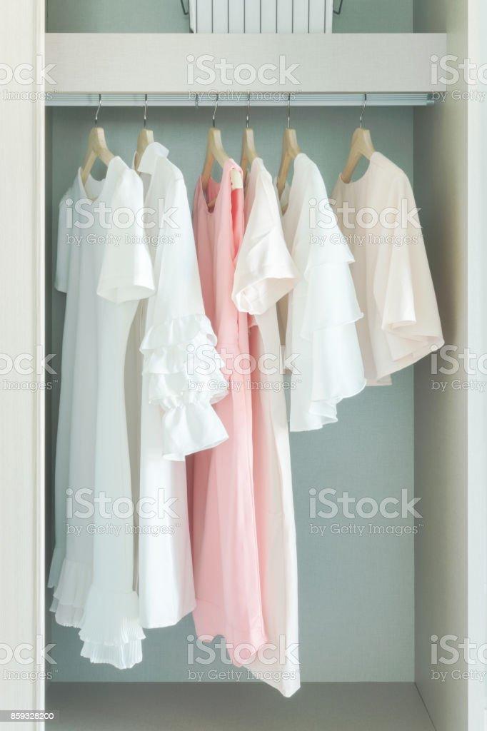 Pastel woman cloths hanging on rail in wardrobe stock photo
