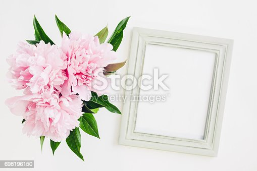 istock Pastel wooden frame decorated with peonies flowers, space for text. mock up 698196150
