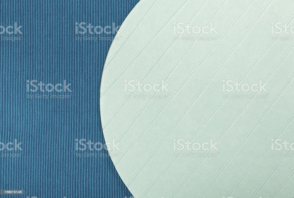 Pastelblue plastic placemat on a blue cotton tablecloth, close-up royalty-free stock photo