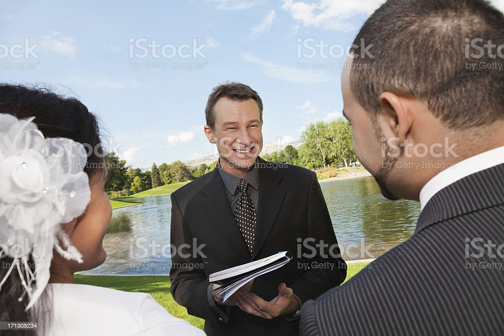Pastor and newly wed couple an outdoor wedding stock photo