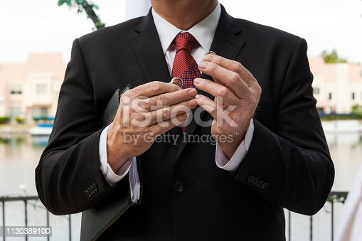 Pastor Holding Wedding Rings In His Hands On Wedding Ceremony, Horizontal Composition