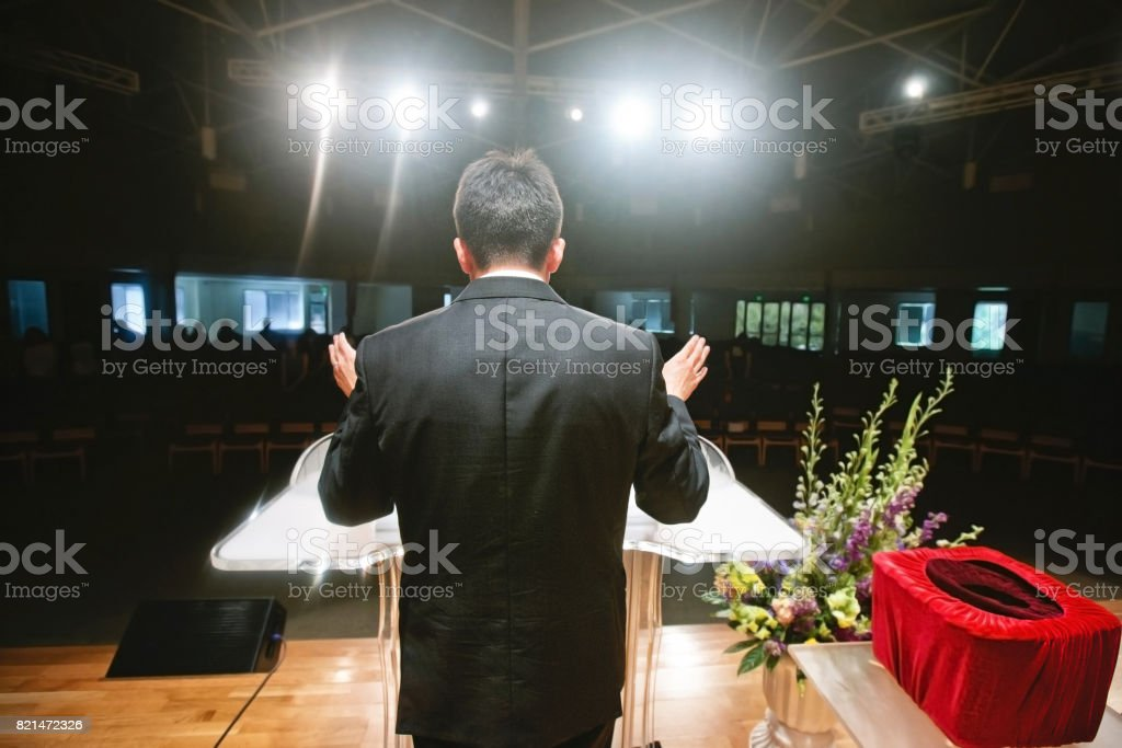 Pastor praying for congregation stock photo