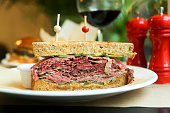 Pastrami on rye sandwich with mustard and red wine