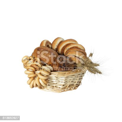 Pastries and bagels with cereal ears in basket isolated on white background