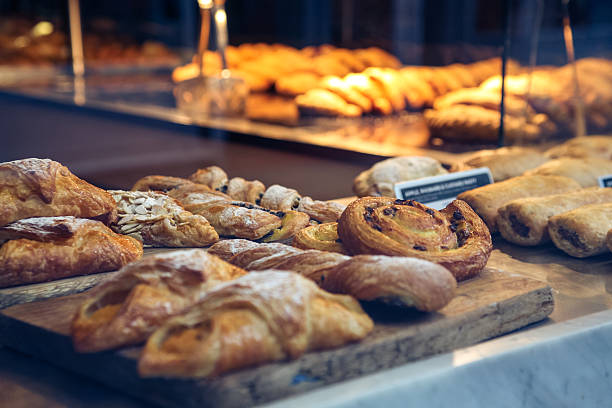 pastries in a bakery window - bakker stockfoto's en -beelden
