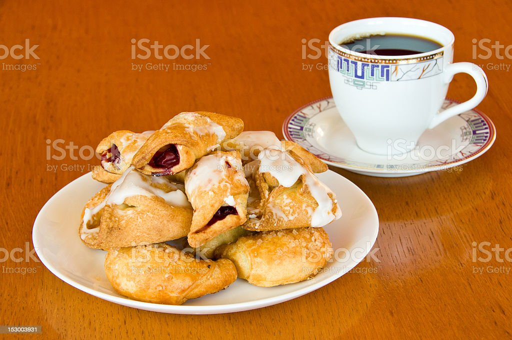 Pastry and a cup of coffee on wooden table stock photo