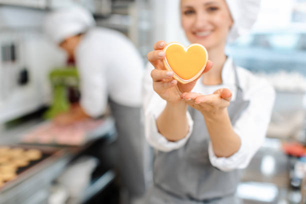 Pastry chef baking heart shaped cookies stock photo