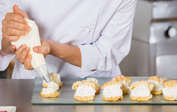 Pastry chef decorating Pastry chef decorating with a sleeve profiteroles icing bag stock pictures, royalty-free photos & images