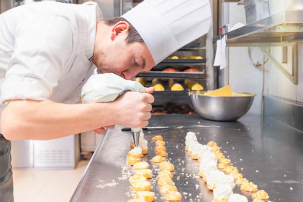 konditor kleingebäck mit spritzbeutel füllen - italienische küchen dekor stock-fotos und bilder