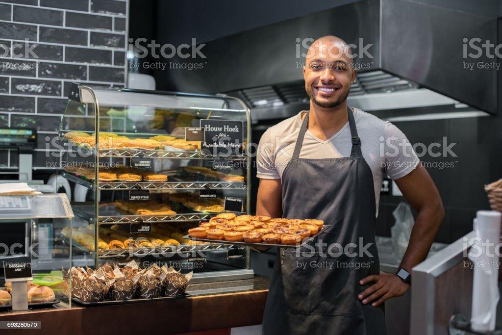 Pastry chef holding small pastry - fotografia de stock