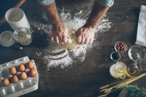 pastry chef kneading dough - impastare foto e immagini stock