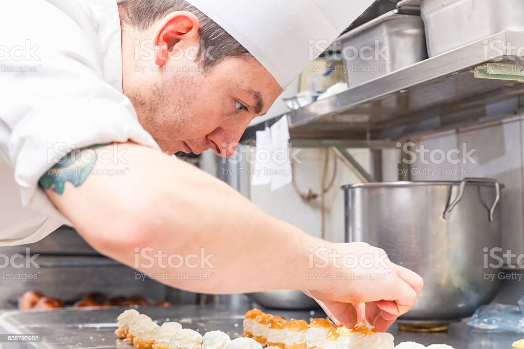 pastry chef preparing small pastries stock photo