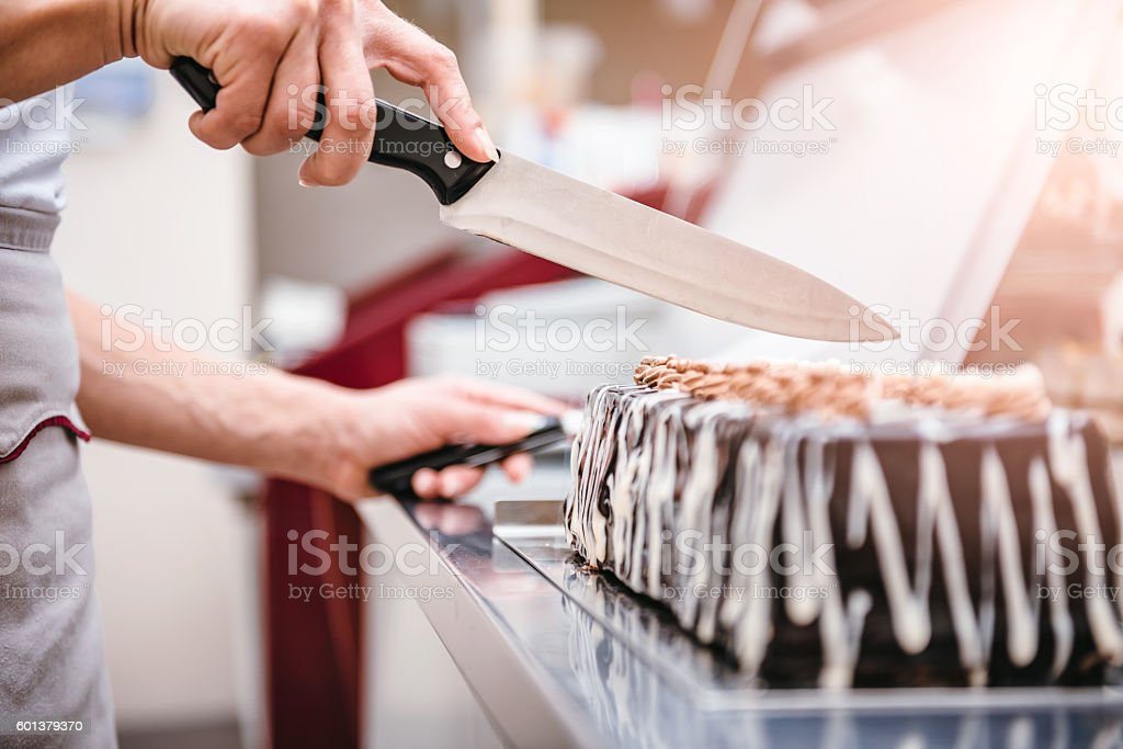 Pastry chef taking slice of cake stock photo