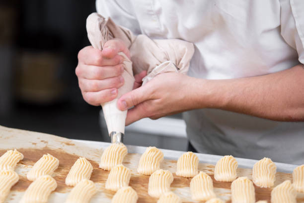 Pastry Chef with confectionary bag pouring cream. Pastry Chef with confectionary bag pouring cream. icing bag stock pictures, royalty-free photos & images