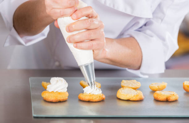 Pastry chef with profiteroles Pastry chef finishing a delicious cream profiteroles icing bag stock pictures, royalty-free photos & images