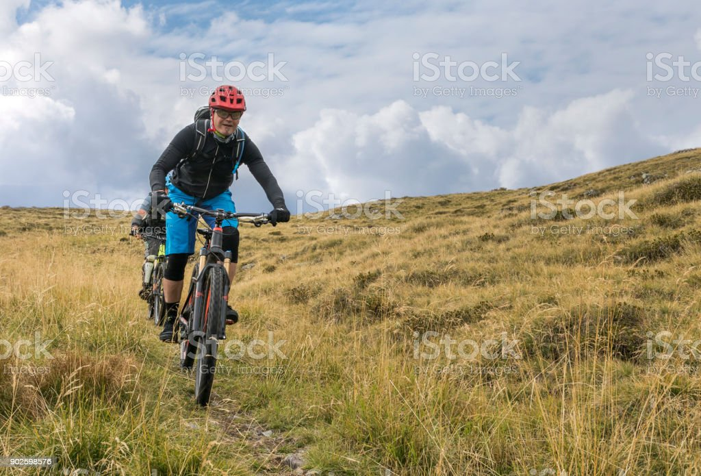 Pasture mountainbiking in the Friulian Mountains, Italy. stock photo