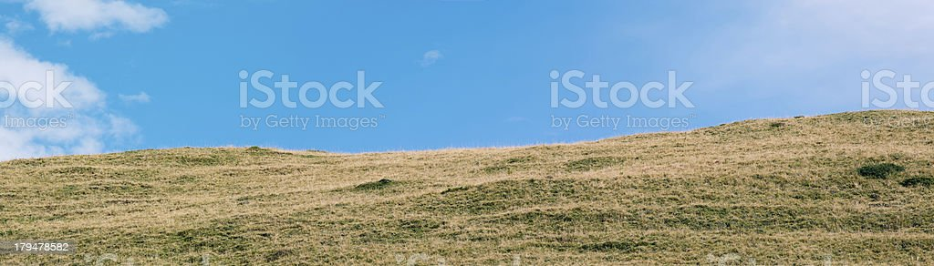 Pasture on a hill with blue sky royalty-free stock photo
