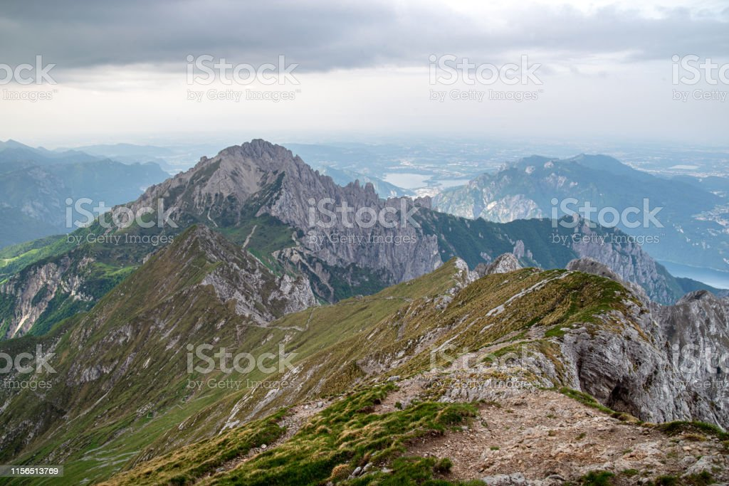 """Pasturo, Lecco, Italy, June 15, 2019 - View on High Crossing to the Southern Grigna, 2184 m (commonly called """"Grignetta"""") taken from refuge Brioschi, on top of the Northern Grigna, 2410 m (commonly called """"Grignone"""") on a cloudy and windy morning - Стоковые фото Альпинизм роялти-фри"""
