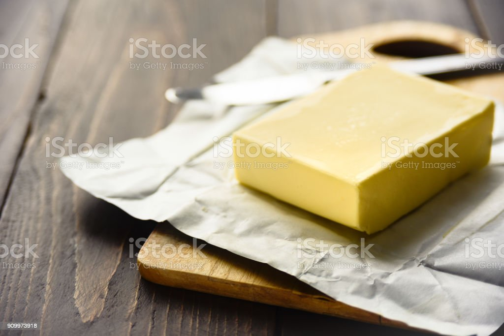 Pat of fresh farm butter with a knife stock photo