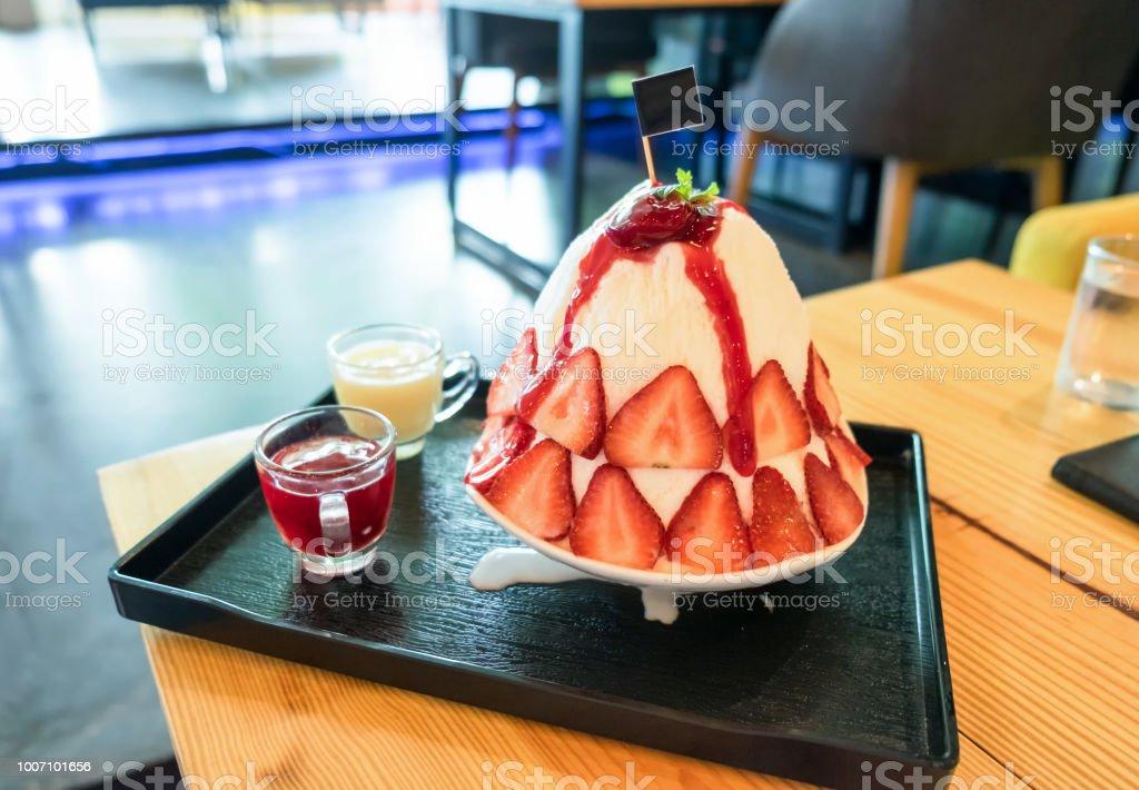 Patbingsu, bingsu 플레이크 얼음 디저트에 연유와 딸기 스톡 사진