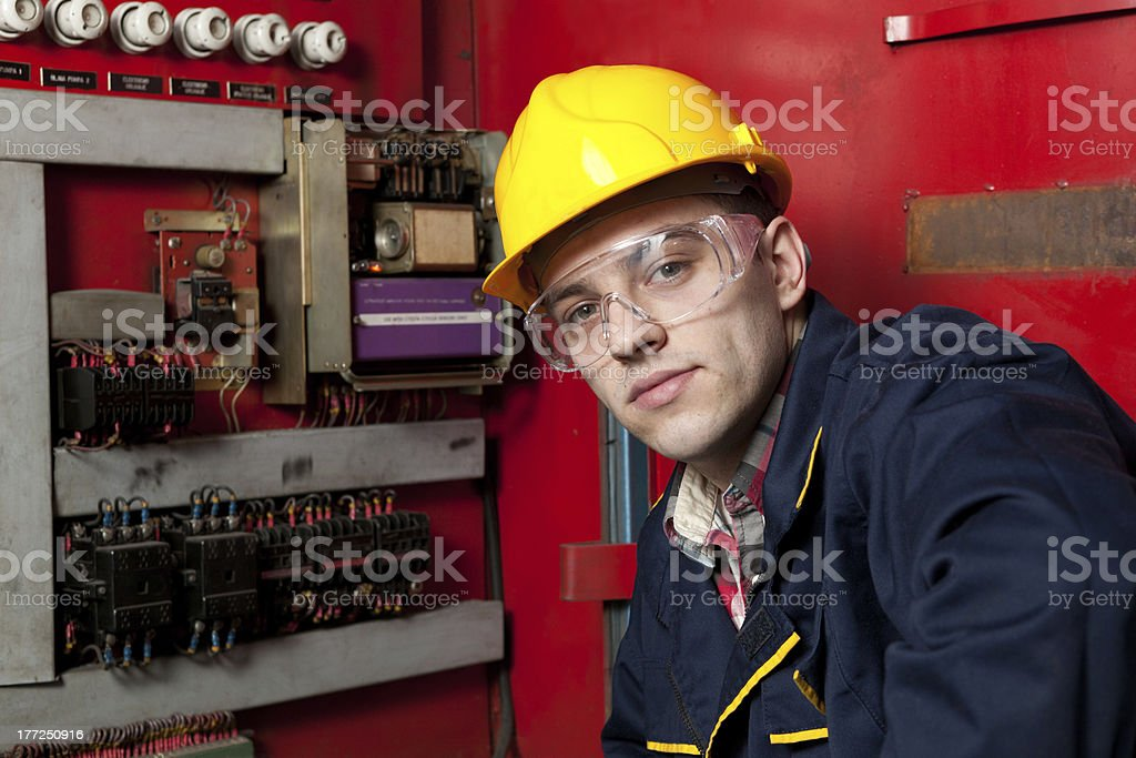 Patch panel inspector in hard hat facing camera by machinery royalty-free stock photo