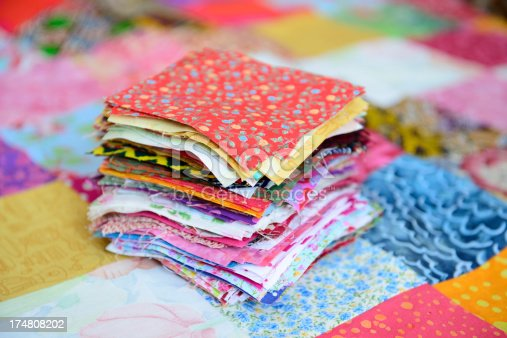 Pile of different colour and patterned material patches for a patchwork quilt.