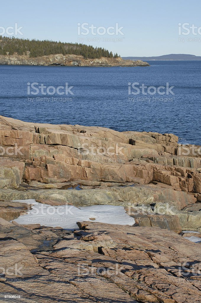 Patches of snow lie on the rocky Maine coast royalty-free stock photo